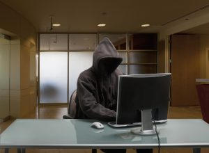 Caucasian man in hoody sitting at office desk
